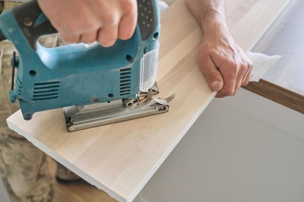 Tischlerhand unter verwendung der professionellen holzbearbeitungselektrowerkzeuge