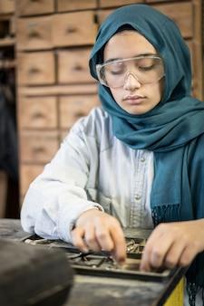 Tischlerwerkstatt mit einem professionellen muslimischen mädchen