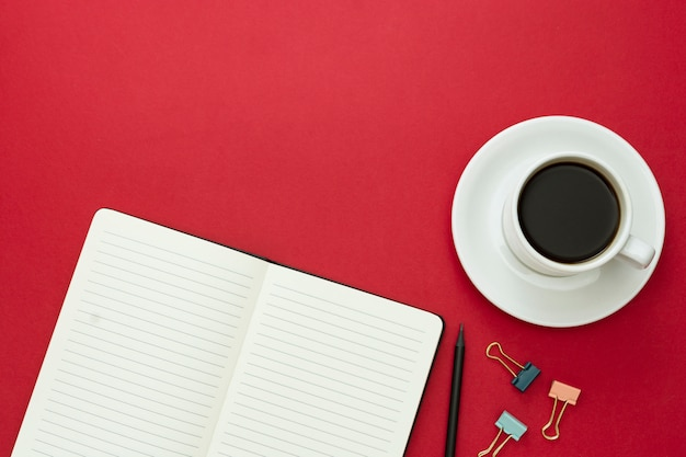 Tischplatte, arbeitsschreibtisch mit offenem notizbuch und kaffeetasse auf rotem hintergrund. kopieren sie platz für text.