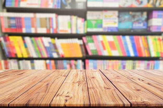 Tischplatte holz schreibtisch und verschwommenes bücherregal im bibliotheksraum, bildungshintergrund, zurück zum schulkonzept