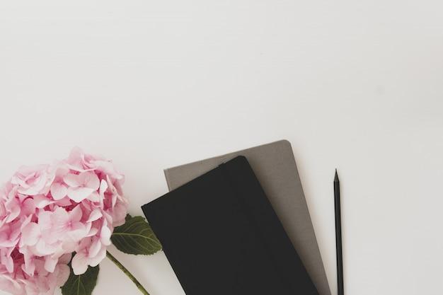 Tischplatte, notizbücher, bleistift und rosa hortensienblume. speicherplatz kopieren.