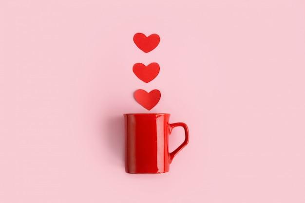 Tischplatteansichtvogelperspektive des zeichenvalentinstag-hintergrundkonzeptes rote kaffeetasse der flachen lageanordnung mit dampfherzform auf modernem rosa schreibtischstudio des papiers zu hause pastelltondesign.