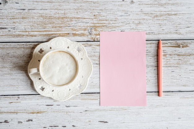 Tischplatteneinzelteile der flachen lage: kaffeetasse, papierfreier raum, stift auf weißem holztisch
