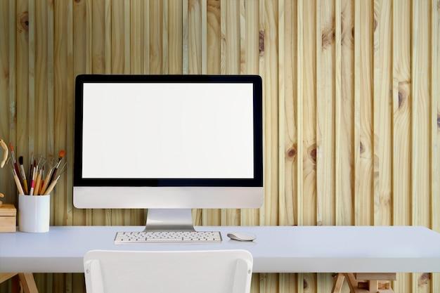 Tischrechner des leeren bildschirms auf weißem schreibtisch über wand im studiobüro.