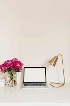 Tischschreibtischarbeitsplatz mit leerem kopierraum, der laptop-bildschirm nachahmt. modernes hauptinnendesign mit blumenstrauß der rosa pfingstrosen, goldene lampe gegen weiße wand.