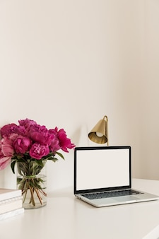 Tischschreibtischarbeitsplatz mit leerem kopierraum, der laptop-bildschirm nachahmt