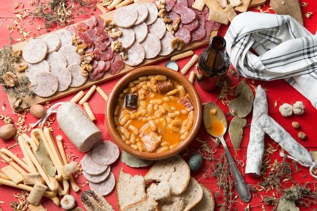 Tischset mit einem asturischen bohneneintopf aus spanien und mehreren vorspeisen mit würstchen