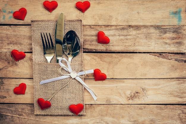 Tischset zum feiern valentinstag. hölzerne tisch platz einstellung und besteck mit roten herzen für valentinstag.