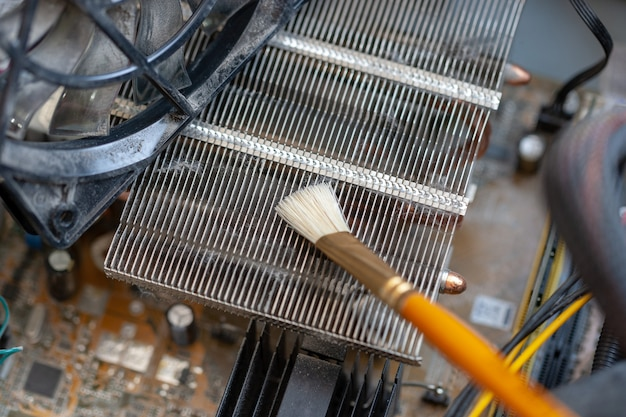 Tischstaubstaubreinigung mit quaste. cpu-kühler-system mit staub und gewebe.