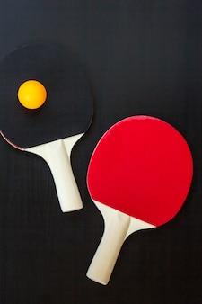 Tischtennis oder tischtennisschläger und ball auf einem schwarzen hintergrund