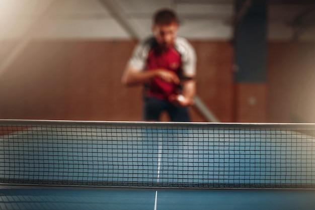 Tischtennisnetz, selektiver fokus, männlicher spieler auf hintergrund. tischtennis training drinnen