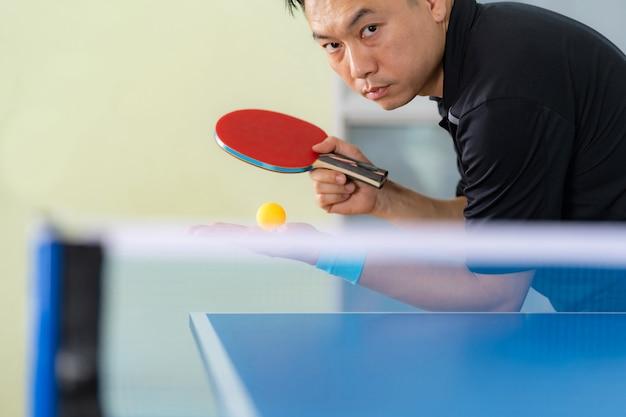 Tischtennisplatte, mann, der tischtennis mit schläger und ball in einer sporthalle spielt