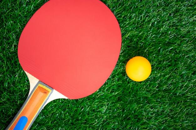 Tischtennisschläger mit orangefarbenen bällen, ping-pong-paddel auf greensward