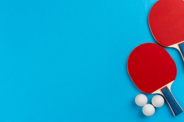 Tischtennisschläger und bälle auf blauer oberfläche