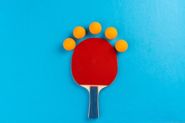 Tischtennisschläger und ball auf blau