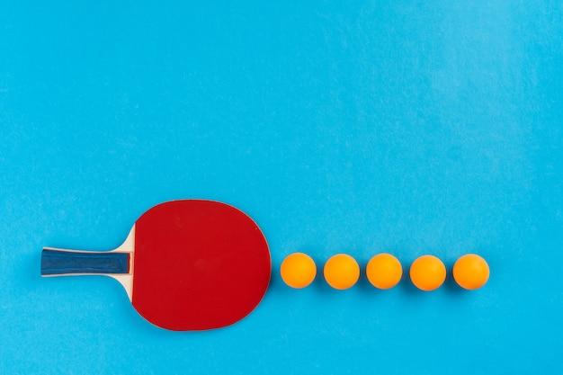 Tischtennisschläger und ball auf blauem hintergrund