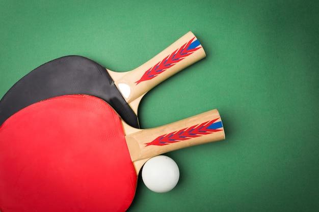 Tischtennisschläger und ball auf dem tisch