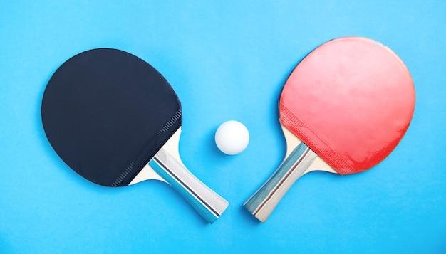 Tischtennisschläger und ein weißer plastikball auf blau