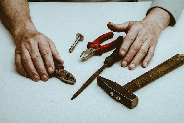 Tischzusammensetzung mit werkzeugen und händen eines älteren arbeiters.