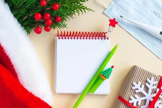 To-do-liste oder wunschliste für weihnachten 2021, stift, natürliche dekorationen sowie medizinische maske und thermometer