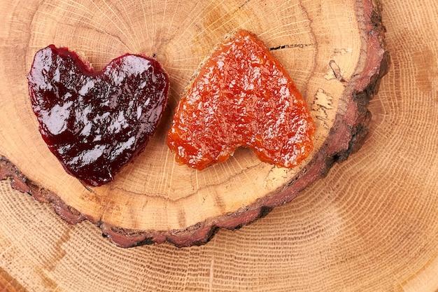 Toast auf holzstammscheibe. gelee-herzförmiges brot. traditionelles süßes frühstück.