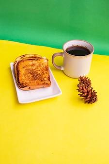 Toast auf weißer platte und schwarzer kaffeetasse mit fichte-blumen-dekoration auf gelbem und grünem papierhintergrund. toast und schwarzer kaffee zum frühstück. vertikales foto