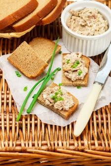 Toast aus roggenbrot mit fischpastete (rillettes) aus geräucherter makrele, frischkäse und frühlingszwiebeln, feinschmeckerische vorspeise, picknick