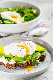 Toast des poschierten eies mit avocado-, frischkäse- und roggenbrot auf grauer platte. gesundes lebensmittelkonzept.