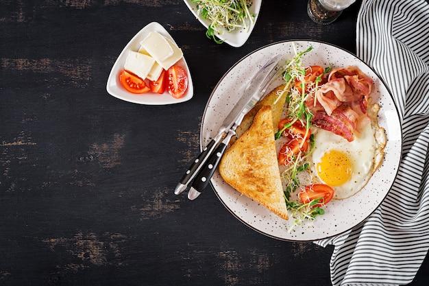 Toast, ei, speck und tomaten sowie microgreens salat