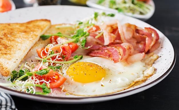 Toast, ei, speck und tomaten und microgreens-salat.