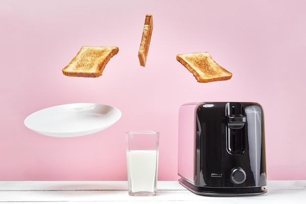 Toast flog aus dem modernen toaster. in der nähe von glas milch. levitation essen und gericht