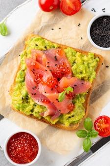 Toast mit avocado, rotem fischkaviar und schwarzem sesam