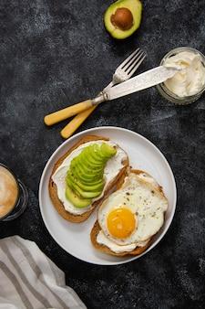 Toast mit avocado und spiegelei zum frühstück.