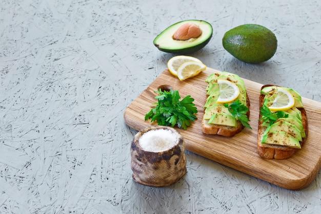 Toast mit avocado, zitrone, paprika oder paprika auf grauem hintergrund