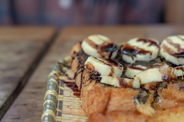 Toast mit bananen, schokolade schocks gekrönt. holz auf ein klassisches gericht