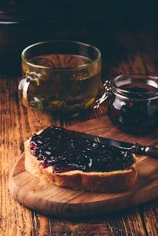 Toast mit beerenmarmelade auf schneidebrett und tasse grünem tee