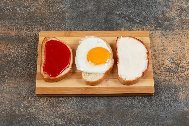 Toast mit ei, frischkäse und marmelade auf holzbrett.