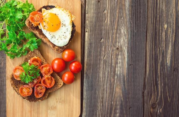 Toast mit ei und gebratenen tomaten auf rustikalem holzhintergrund. gesundes frühstück.