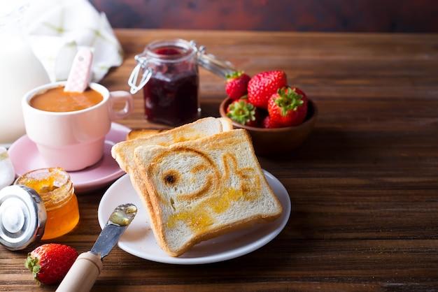 Toast mit einem lächeln, marmelade, kaffee und frischen erdbeeren zum frühstück