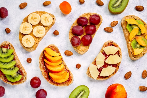 Toast mit erdnussbutter, erdbeermarmelade, banane, trauben, pfirsich, kiwi, ananas, nüssen