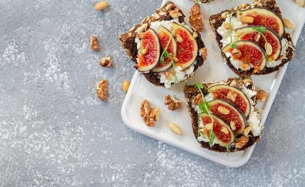 Toast mit feigen, käse, honig, kräutern und nüssen. köstliches frühstück auf draufsicht der weißen tafel. gesundes lebensmittelkonzept.