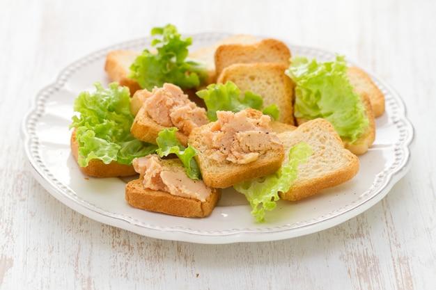 Toast mit fischpastete auf weißer platte