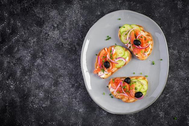 Toast mit frischkäse, räucherlachs, gurke, schwarzen oliven und roten zwiebeln. offene sandwiches. gesunde pflege, super-food-konzept. draufsicht, überkopf