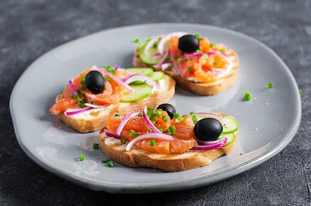 Toast mit frischkäse, räucherlachs, gurke, schwarzen oliven und roten zwiebeln. offene sandwiches. gesunde pflege, super-food-konzept.