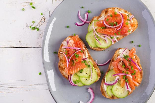 Toast mit frischkäse, räucherlachs, gurke und roter zwiebel auf rustikalem holztisch. offene sandwiches. gesunde pflege, super-food-konzept. draufsicht, überkopf
