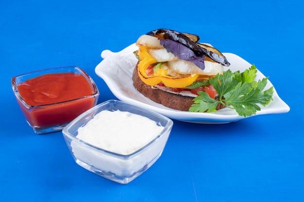 Toast mit gebratenem gemüse auf blattförmigem teller auf blauer oberfläche