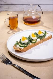 Toast mit geröstetem brot, weich gekochten eiern mit gelbem eigelb und mit kräutern auf weißem teller auf leuchttisch.