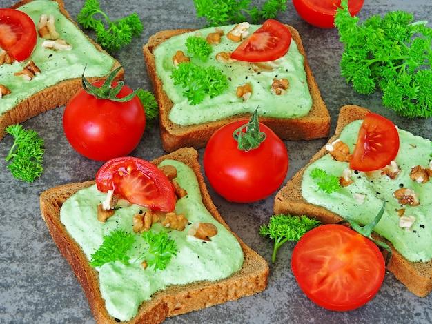 Toast mit grünem hüttenkäse und walnüssen und tomate.