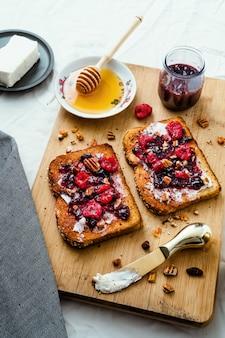 Toast mit honig, frischkäse und marmelade aus roten beeren