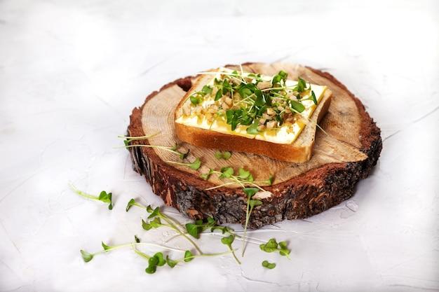 Toast mit käse, sprossen und walnüssen auf einem holzständer.